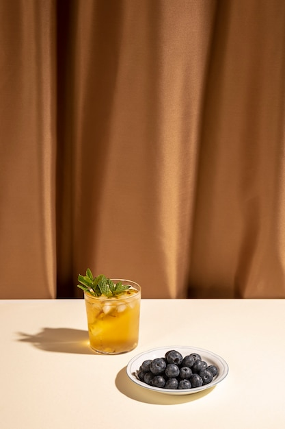 Homemade cocktail drink glass with blueberries on plate over white table near brown curtain Free Photo