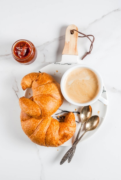 Homemade continental breakfast, coffee croissants. jam on white marble table, copyspace top view Premium Photo