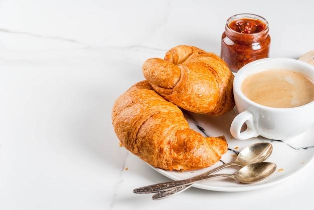 Homemade continental breakfast, coffee croissants. jam on white marble table, copyspace Premium Photo