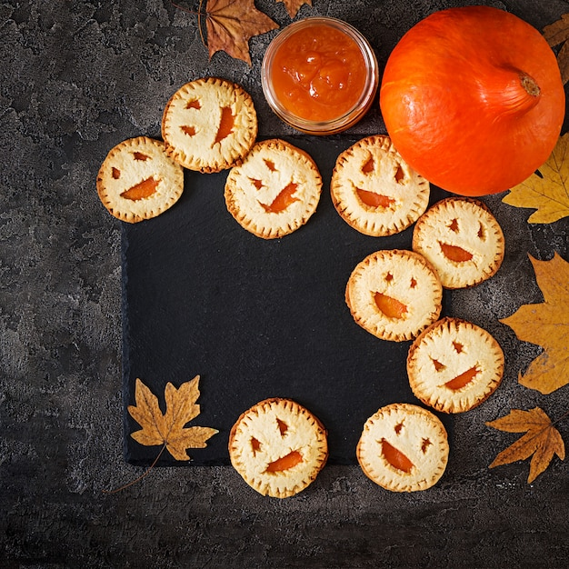 Homemade  cookies in the form as halloween  jack-o-lantern pumpkins  on the dark table. top view. Free Photo