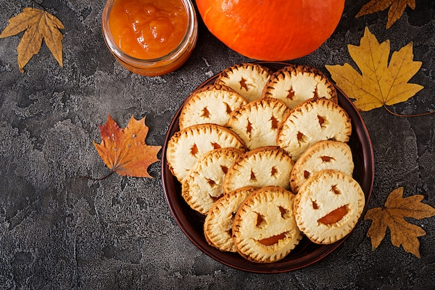 Homemade  cookies in the form as halloween  jack-o-lantern pumpkins  on the dark table. Premium Photo