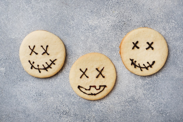 Homemade cookies for halloween, cookies with funny faces and spider webs Premium Photo