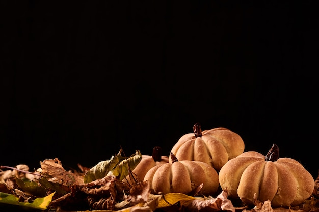 Homemade cookies in shape of pumpkin in autumn leaves. halloween handmade cookies in background with copyspace Premium Photo