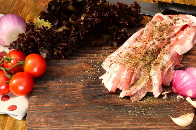 Homemade cooking. products for delicious food. sprinkle with spices sliced raw pork or beef brisket on wooden kitchen board. Premium Photo