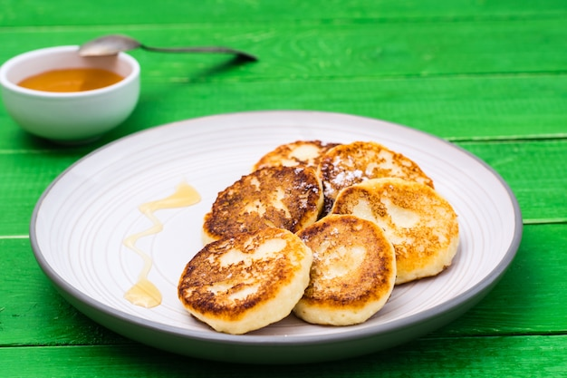 Homemade cottage cheese pancakes with honey on a plate on a wooden table Premium Photo
