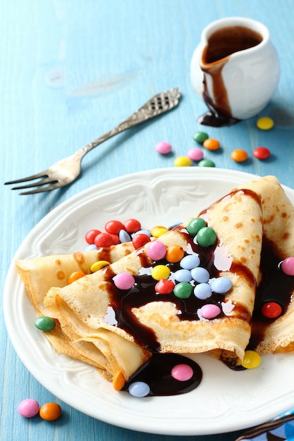 Homemade crepes with multicolored dragee and chocolate sauce on blue wooden background Premium Photo