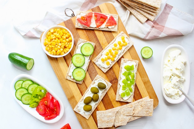 Homemade crispbread toast with cottage cheese and green olives, slices of cabbage, tomatoes, corn, green pepper on cutting board. healthy food concept, top view. flat lay Free Photo