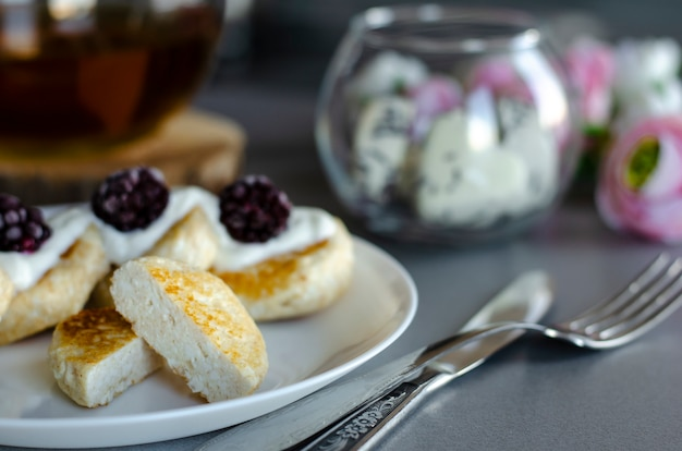 Homemade curd cheese pancakes with sour cream and blackberries for breakfast Premium Photo