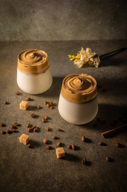 Homemade dalgona coffee on dark background next to coffee beans and cane sugar trendy fluffy creamy whipped drink made by instant coffee sugar and milk low key copy space Premium Photo