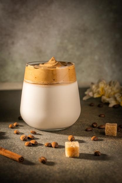 Homemade dalgona coffee on dark background. next to coffee beans and cane sugar. Premium Photo