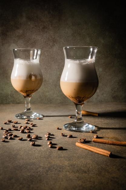 Homemade dalgona coffee on dark background. next to coffee beans and cinnamon sticks. Premium Photo