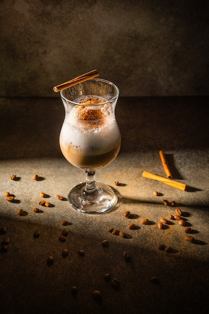 Homemade dalgona coffee on dark background. next to coffee beans and cinnamon sticks. Premium Photo
