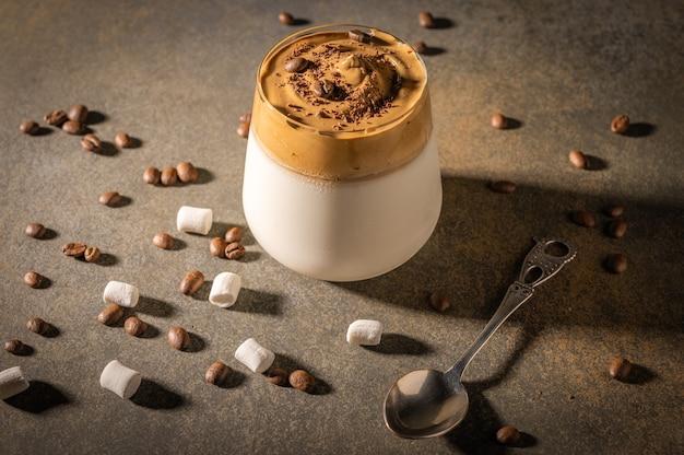 Homemade dalgona coffee on dark background. next to coffee beans and marshmallows. Premium Photo