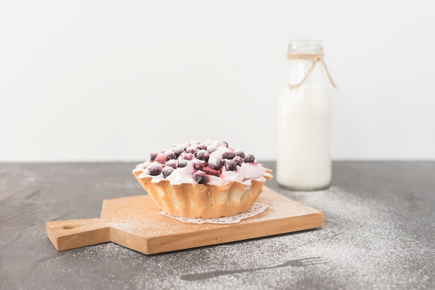 Homemade delicious blueberries tart on chopping board with milk bottle Free Photo