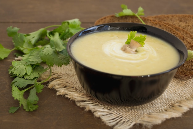 Homemade diet mushroom soup on a wooden table. Premium Photo