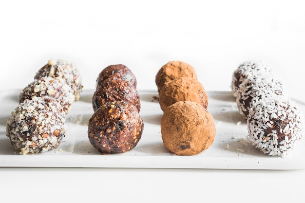 Homemade energy bites, vegan chocolate truffle with cacao and coconut flakes. concept healthy food. Premium Photo