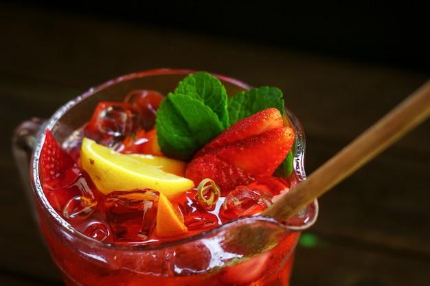 Homemade fresh strawberry lemonade with fresh fruit in a jar on black background Premium Photo