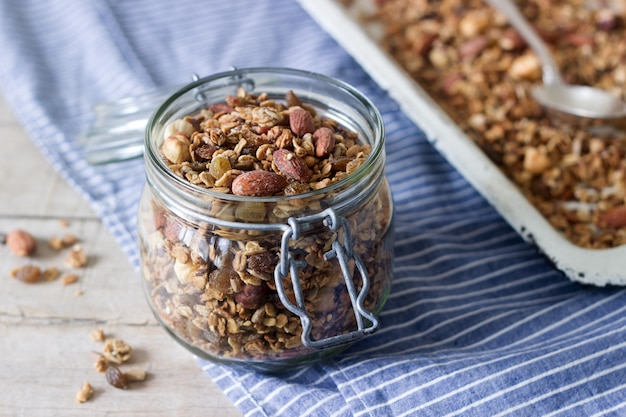 Homemade granola in a glass jar and on a baking sheet. Premium Photo