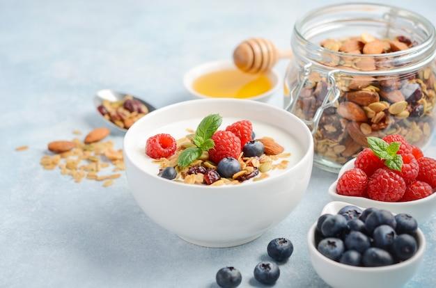 Homemade granola with yogurt and fresh berries, healthy breakfast concept. Premium Photo