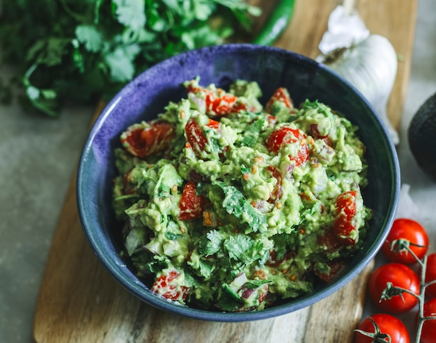 Homemade guacamole with cherry tomatoes food photography recipe idea Premium Photo