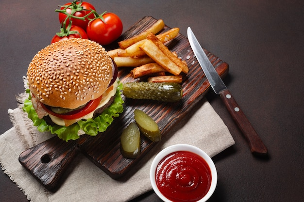 Homemade hamburger with ingredients beef, tomatos, lettuce, cheese, onion, cucumbers and french fries Premium Photo