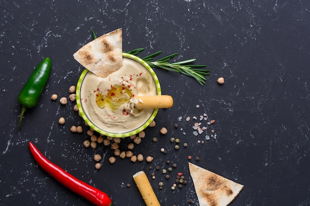 Homemade hummus with pita and grissini bread sticks, chilli, jalapeno on black stone table. middle eastern traditional and authentic arab cuisine. top view, flat lay Premium Photo