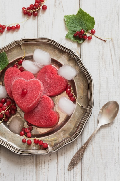 Homemade ice cream of red currant in shape of heart and on vintage dish and wooden background. Premium Photo