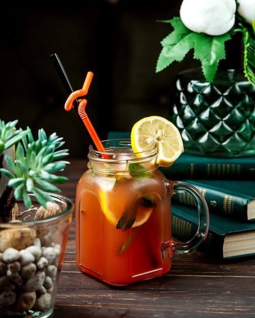 Homemade ice tea with herbs and lemon on top Free Photo