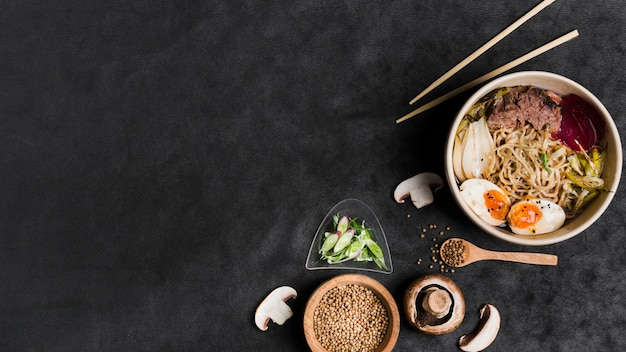 Homemade japanese pork ramen noodles with eggs and ingredients on black backdrop Free Photo