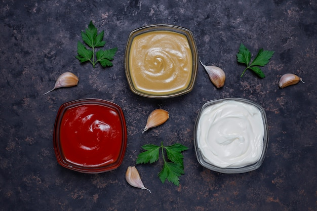 Homemade ketchup,mustard and mayonnaise sauce and ingredients on dark . top view Free Photo