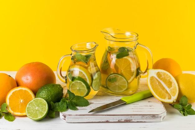 Homemade lemonade jugs with yellow background Free Photo