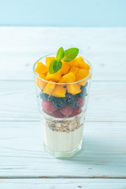 Домашнее манго, малина и черника с йогуртом и мюсли - стиль здорового питания Premium Фотографии