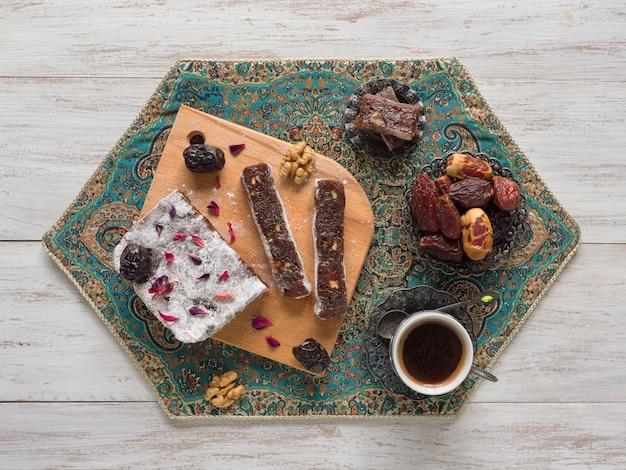 Домашние мармеладные сладости с финиковыми фруктами и орехами, восточные конфеты на белой деревянной поверхности. Premium Фотографии
