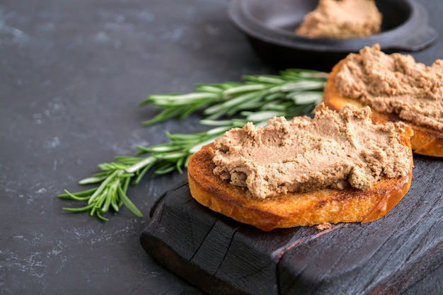Homemade meat pate on toasted crusty bread. dark photo style. Premium Photo