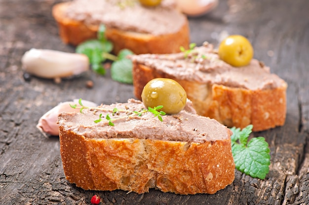 Homemade meat snack chicken liver pate with savory and olives Premium Photo