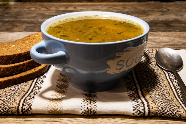 Homemade meat soup in a ceramic blue bowl, metal spoon, folklor napkin on a wooden table. Premium Photo