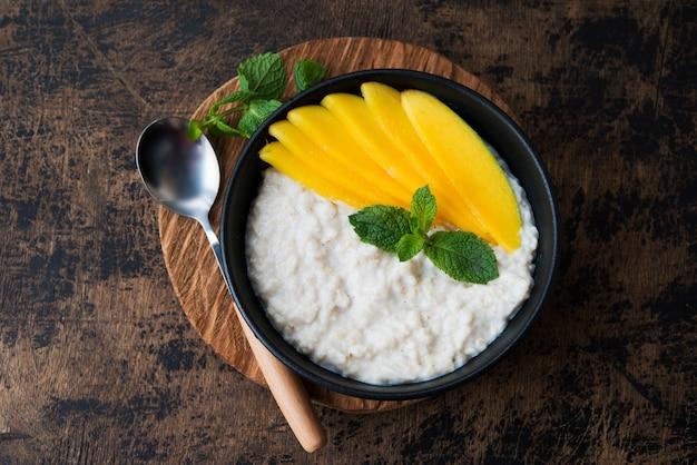 Домашняя овсяная миска с молоком и свежими ломтиками манго Premium Фотографии