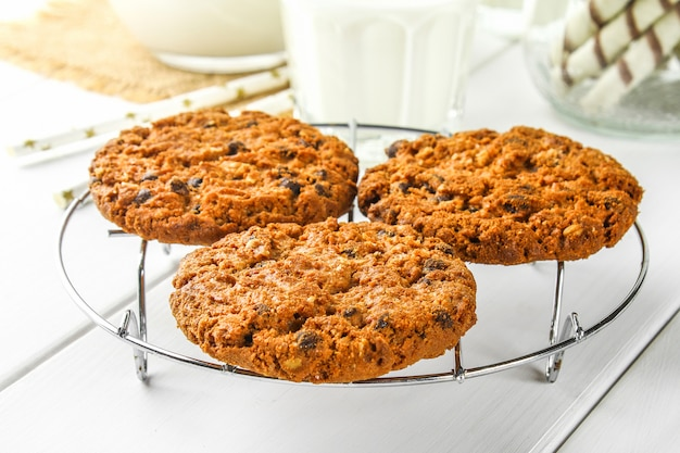 Homemade oatmeal cookies. cookies on an iron grate on a wooden white table. Premium Photo