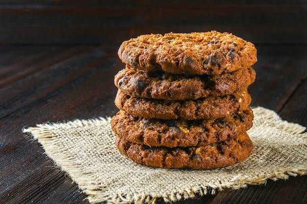 Homemade oatmeal cookies. a stack of sackcloth on a brown wooden table. Premium Photo