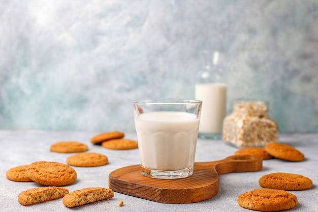 一杯の牛乳と自家製オートミールクッキー。 無料写真