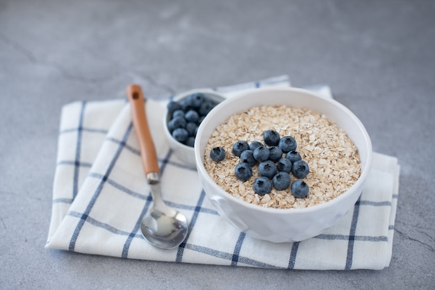 Homemade oatmeal with blueberries and strawberries in bowl on gray Premium Photo
