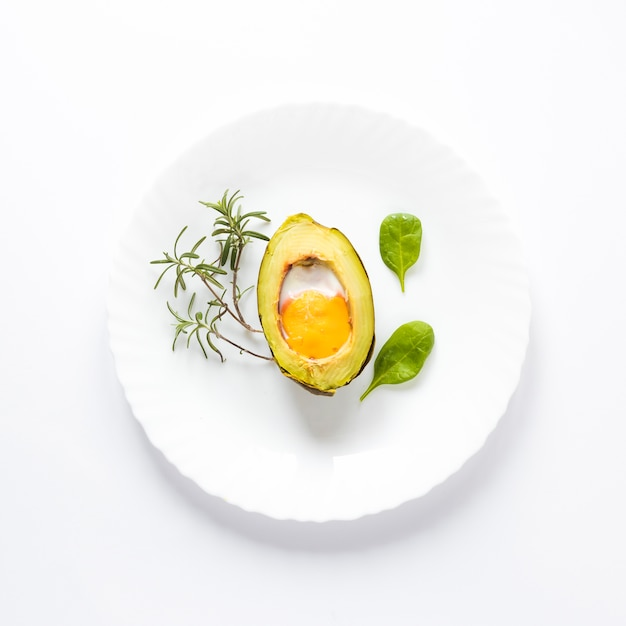 Homemade organic egg baked in avocado with leaves on white background Free Photo