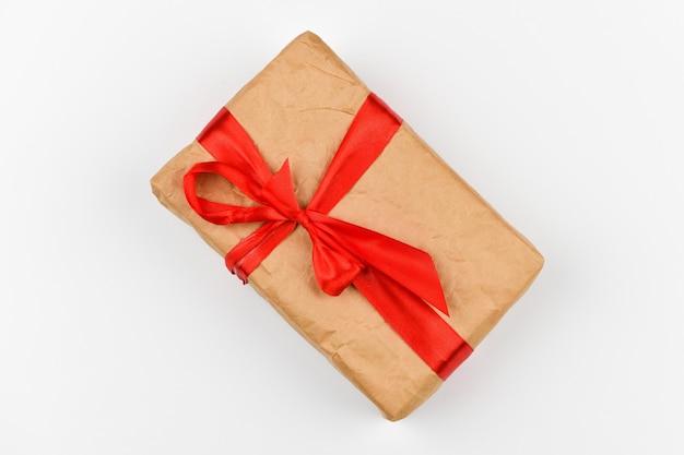 Самодельная подарочная упаковка из бумаги с красным бантом на белом пространстве. хвойные зеленые ветви на белом пространстве. вид сверху. место для письма. рождественское пространство. Premium Фотографии