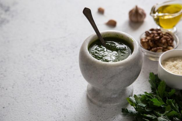 Homemade parsley pesto sauce and ingredients, vegan healthy food. Premium Photo