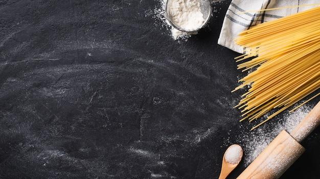 Домашняя паста спагетти, делая фон на черной текстуре, копией пространства, вид сверху, баннер Premium Фотографии