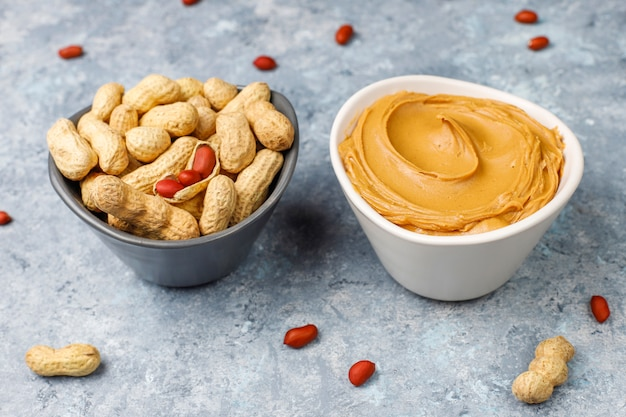 Homemade peanut butter with peanuts on grey concrete table, top view Free Photo
