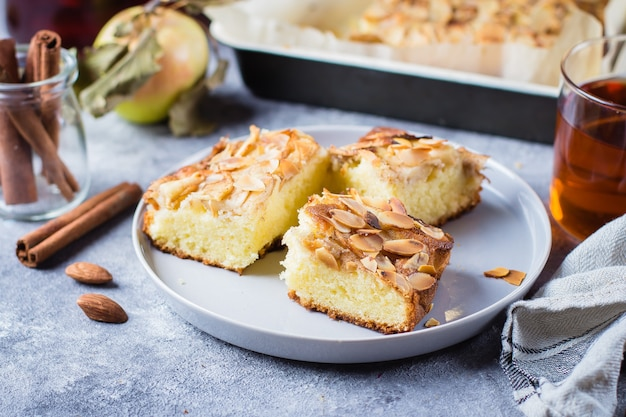 Homemade pies with apples and almond flakes. norwegian biscuit pie on stone table background Premium Photo