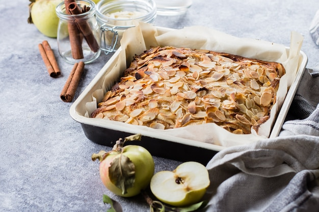 Homemade pies with apples and almond flakes on stone concrete table background. scandinavia kitchen Premium Photo