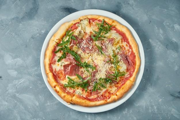ハモン、ルッコラ、パルメザンチーズ、コンクリートの表面に白い皿に自家製ピザ。閉じる。セレクティブフォーカス Premium写真