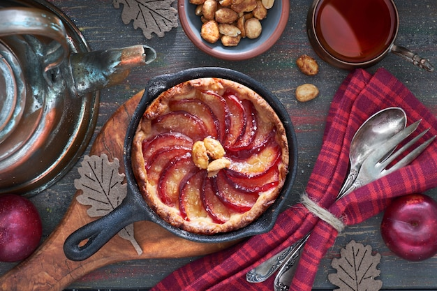 Homemade plum tart baked in iron cast skillet served with peanuts on wood Premium Photo